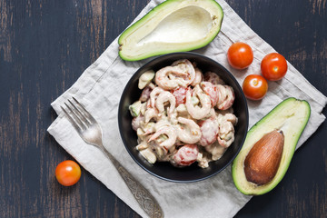 Salad with avocado shrimp and tomato sauce served in a black bowl.