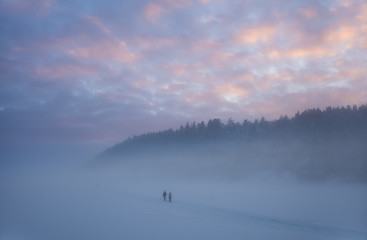 Two skiers coming out of the mist in the forests after sunset. Oslo, Norway