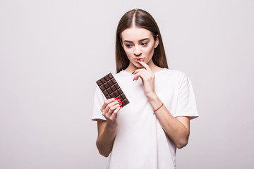 Young healthy thoughtful girl with chocolate isolated on gray background. Health concept.