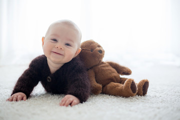 Little cute baby boy, dressed in handmade knitted brown teddy bear overall