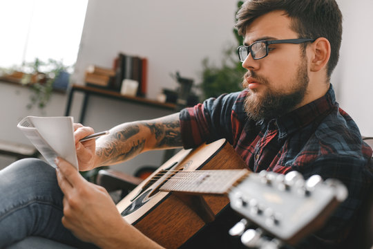 Young guitarist hipster at home with guitar sitting writing melody inspired