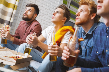 Men watching sport on tv together at home football championship