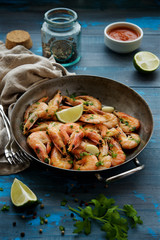 Shrimp fried in a frying pan with garlic and spices. Blue wooden nautical background