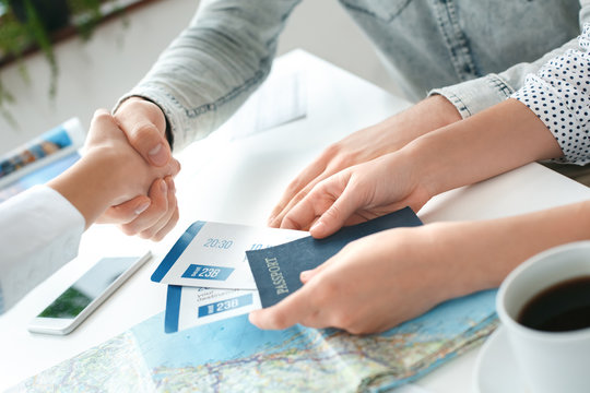 Young couple in a tour agency communication with a travel agent travelling concept shaking hands