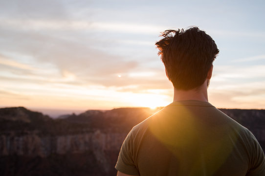 A man standing, looking out at the Grand Canyon during sunset.