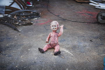 Dirty plastic naked baby doll sitting on the ground in front of a metal shop waving