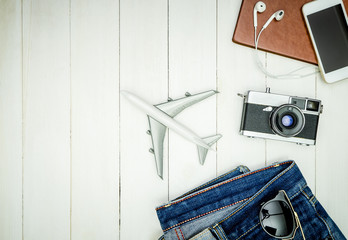 Hipster travel objects and gadgets on white wooden copy space