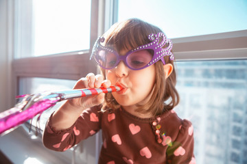 Portrait of Caucasian girl child sitting on window sill at home and blowing whistle trumpet celebrating birthday. Toddler preschooler wearing funny glasses, playing, having fun indoors