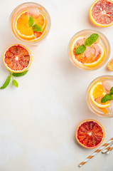 Cold refreshing drink with blood orange slices in a glass on a white concrete background. Top view, flat lay, copy space.