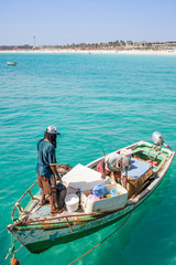 Fishermen on an old fishing boat at the pier and coast of Santa Maria, Sal, Cape Verde