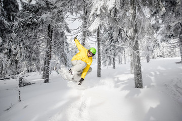 Man riding extremely a snowboard in the snowy forest jumping over the hump