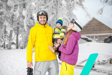 Portrait of a happy family with baby boy standing in winter spots clothes outdoors during the winter vacations