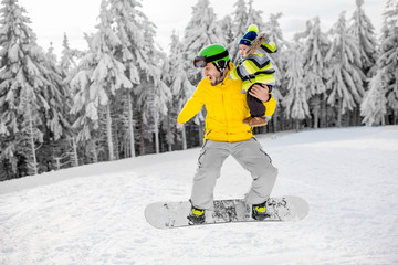 Man in colorful sports clothes riding the snowboard on the snowy mountains with beautiful trees on the background