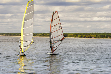A pair of windsurfing plays in the waves, in the vastness of the reservoir