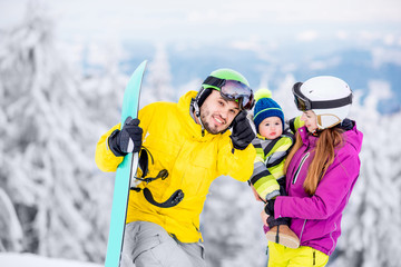 Portrait of a happy family with baby boy in winter sports clothes standing with snowboard during the winter vacations