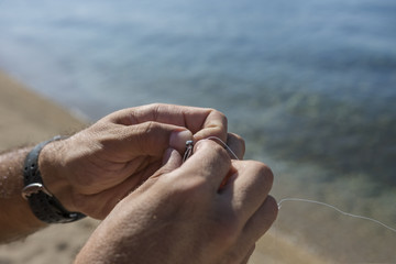 A man knots a fishing hook and lead at the beach