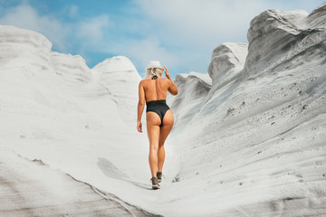 Sexy back of a beautiful woman in a bikini in the white desert background. Lifestyle traveler