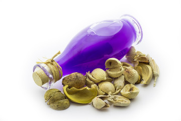 Bottle with purple oil and shell on a white background
