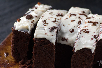 sliced chocolate cake with white icing and chocolate shavings closeup