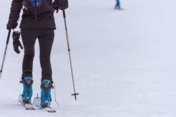 woman with a backpack going on skiing in the snow