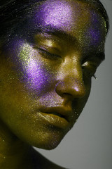 Creative make-up and beauty theme: beautiful girl model with cosmic make-up on face and body green and blue skin color on dark background in studio
