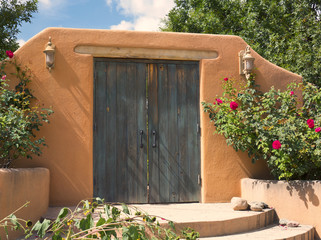 Southwest Style Old Wooden Plank Doors in Adobe Wall with Lanterns