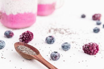 chia with yoghurt, frozen bananas and wild berries, on a white background