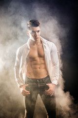 Handsome young muscular man shirtless wearing jeans, taking off leather jacket on naked muscle torso, on dark background in studio shot