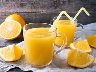 Fresh orange juice on wooden background, rustic style