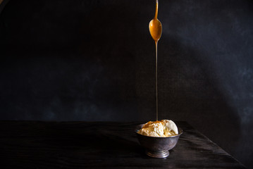 A pewter dish of vanilla ice cream with caramel sauce being drizzled on it.