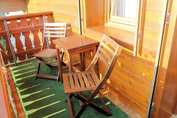 wooden balcony with table and two chairs