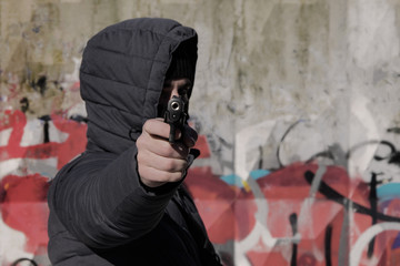 .A criminal in a mask and a hood with weapons in his hands. Toned
