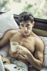 Sexy handsome young man laying shirtless on his bed next to window, holding a coffee or tea cup