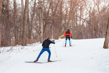Two cross-country skiers training on a cross-country ski run in the forest