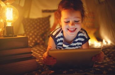 happy child girl with tablet pc laughing in dark in tent at home