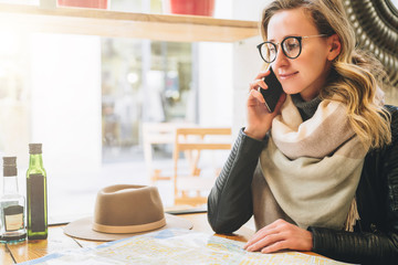 Young female tourist in eyeglasses is sitting in cafe at table and talking on cell phone. Girl is calling her friend on phone. There is map and hat on table. Tourism, travel, vacation.
