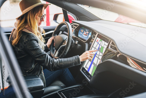 Young woman sits behind wheel in car and uses an electronic