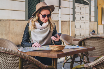 Young woman tourist in sunglasses and hat is sitting in street cafe at table, looking for a way on map, using smartphone. Girl uses digital gadget. Tourism, travel, vacation.