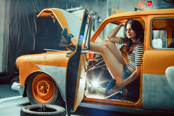 Woman mechanic with screwdriver in sexy shorts