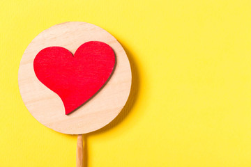 Valentine day concept. Red decorative heart with a stick on yellow background. Free space for your text.