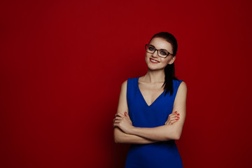 portrait of the stylish sexy woman of the brunette in a blue dress and fashion glasses against the background of a red wall. Studio picture.
