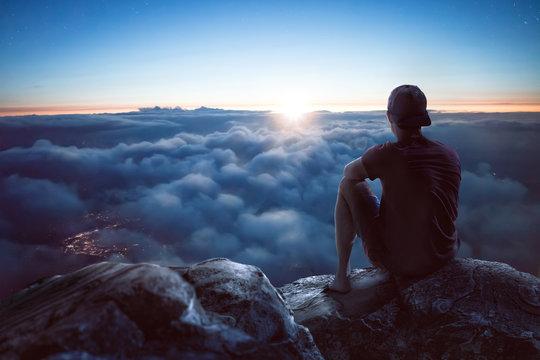Junger Mann mit weitem Blick über die Wolken