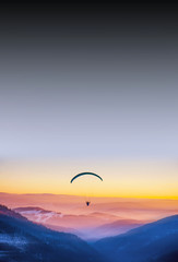 Foto op Canvas Luchtsport Paraglide in beautiful evening light. Mountains in background.