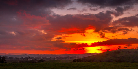 A broad and expansive view of setting sun with red to yellow colored clouds. Oak trees are silhouetted against the red sky. A small community of houses can be seen on the left.