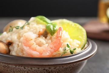 Bowl with delicious seafood risotto on table, closeup