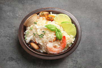 Bowl with delicious seafood risotto on table