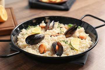 Dish with delicious seafood risotto on wooden table
