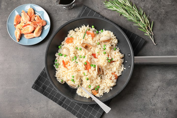 Frying pan with delicious seafood risotto on table