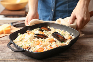 Woman with frying pan of delicious seafood risotto at wooden table