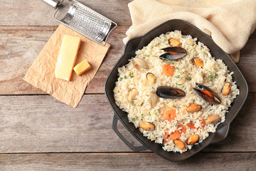 Frying pan with delicious seafood risotto on wooden table